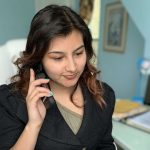Woman at home desk on cellphone