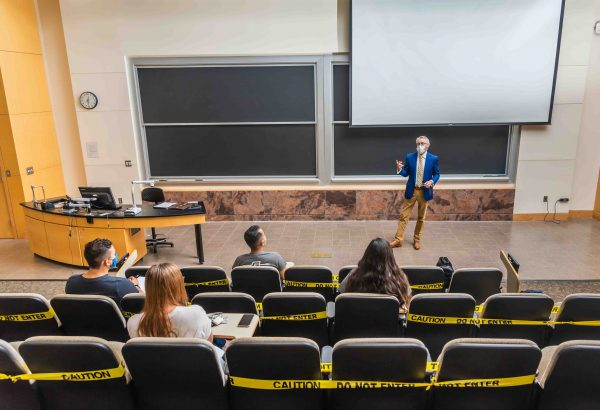 Image of Professor teaching lecture with face mask and social distancing