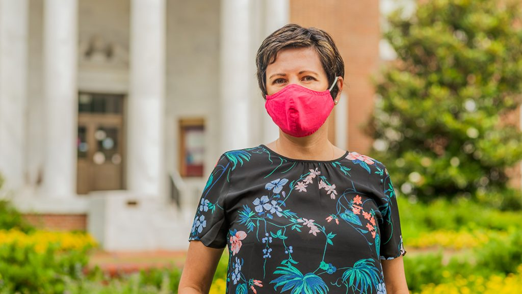 Woman wearing a mask stands in front of campus building