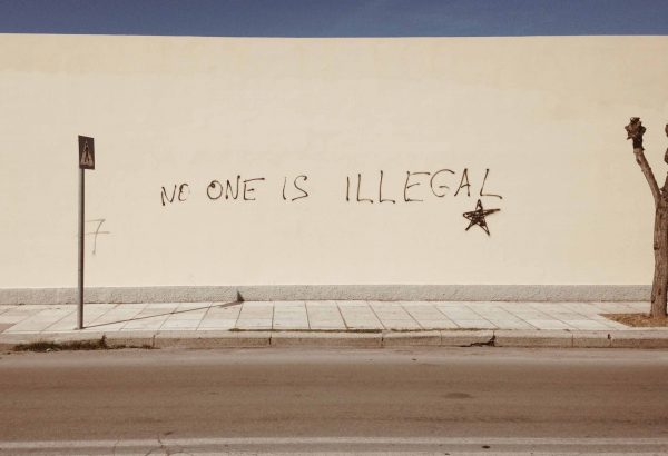 """Walll with """"No One Is Illegal"""" spray-painted on it"""