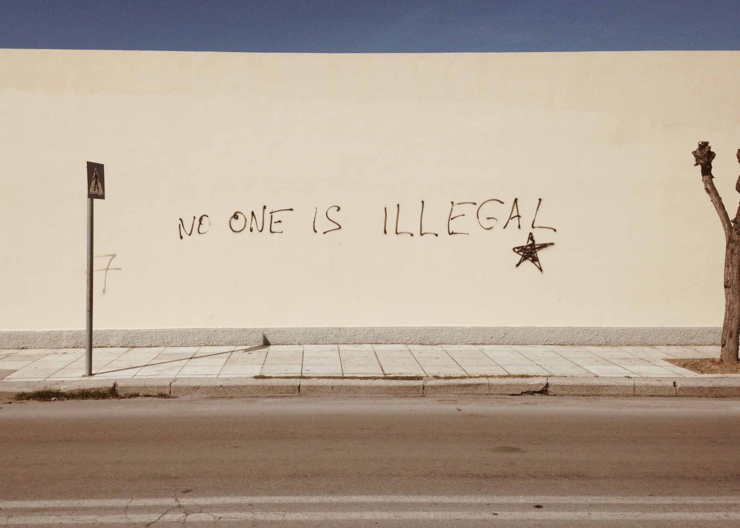 "Walll with ""No One Is Illegal"" spray-painted on it"