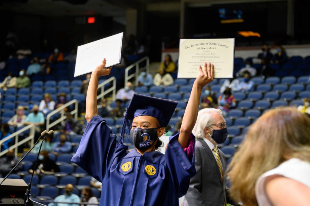 Grad holds up two diplomas