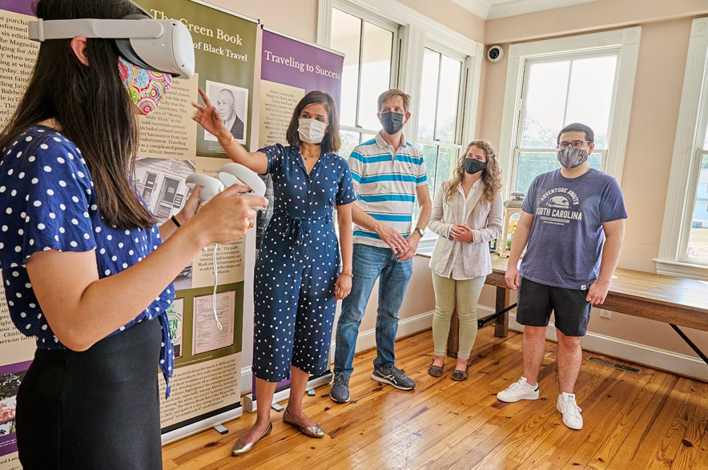 Woman with VR headset is watched by masked people